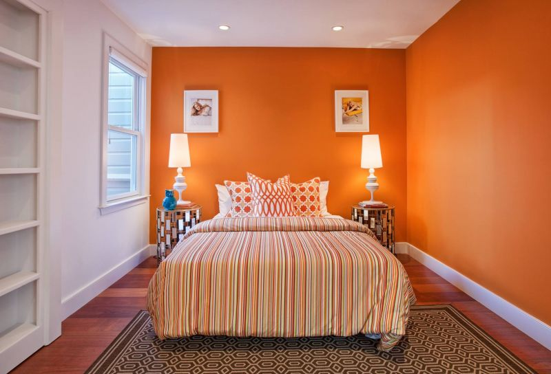 beautiful-interior-design-white-orange-that-has-wooden-floor-with-motifs-carpet-can-add-the-beauty-inside-the-modern-bedroom-with-warm-table-lamp-inside-room