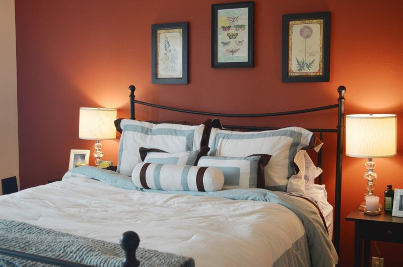 orange-accents-wall-painted-of-modern-bedroom-design-idea-feat-beautiful-wall-artwork-design-and-likeable-iron-beds-surround-with-charming-beam-table-lamp