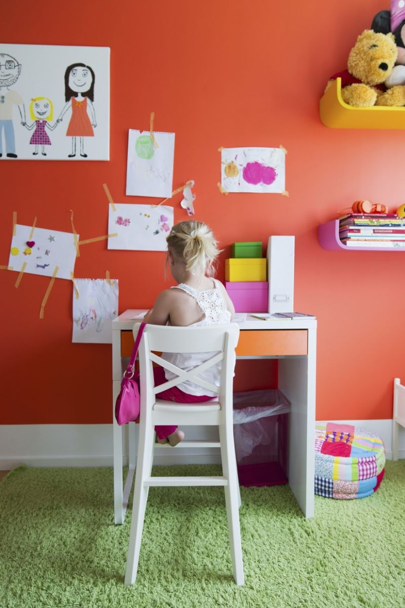 Detail of colourful child's bedroom; child sat on tall, white chair at desk and child's drawings on orange wall