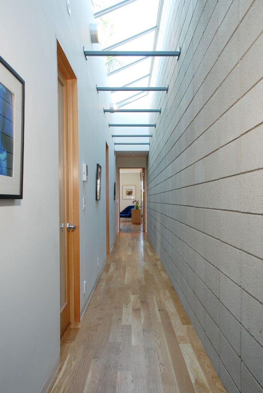 narrow-long-hallway-with-contemporary-lighting-ideas-feat-light-wood-interior-door-and-wall-art-decor-918x1371